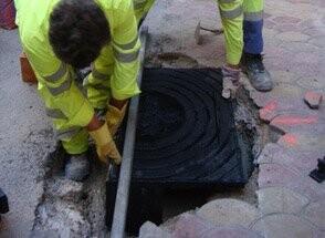 Operarios instalando imbornales en la ciudad de Valencia