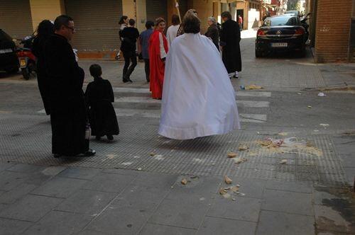 Unos cofrades atraviesan una calle con basura en el suelo/aavv cabanyal-canyamelar
