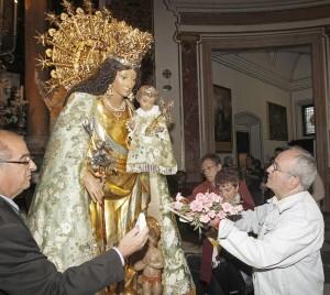 Un hombre acerca a un niño a la Virgen/alberto saiz