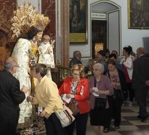 Un mujer besa la mano de la imagen Peregrina de la Virgen de los Desamparados/alberto saiz