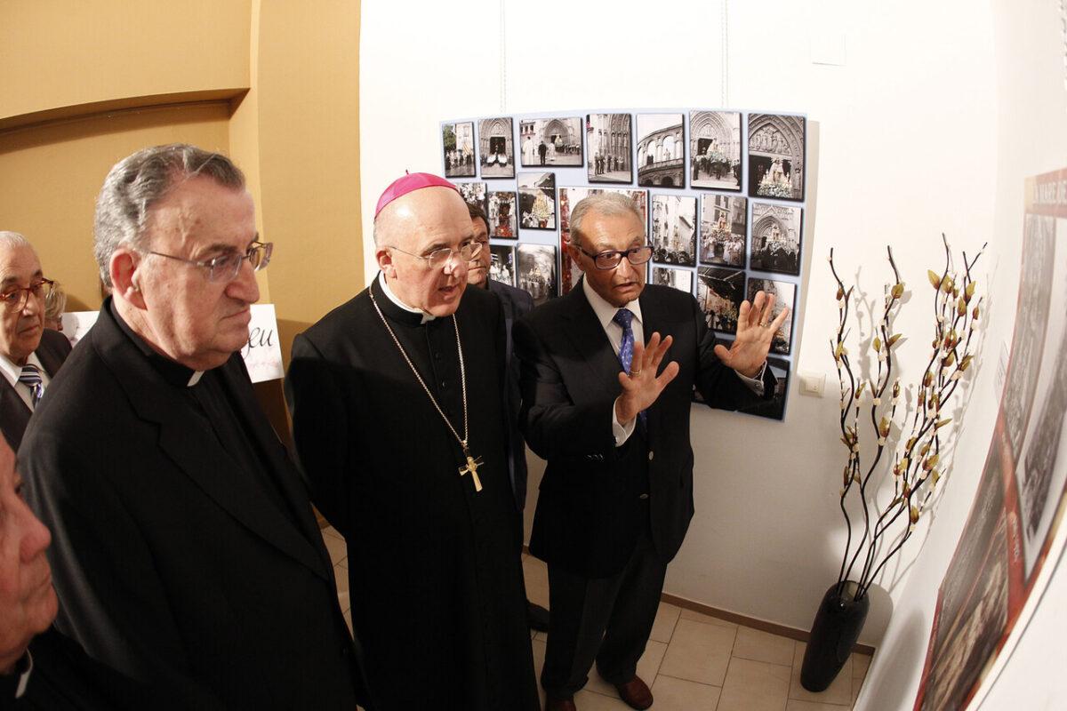 El fotográfo Antonio Sanchis explica al arzobispo varias fotos de la exposición/alberto saiz