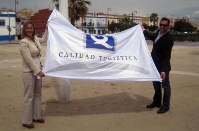 La edil de Playas, Lourdes Bernal, muestra la enseña antes de izarla en la playa del Cabanyal