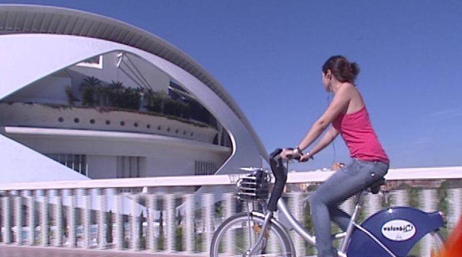 Un mujer en una bici del servicio de Valenbisi pasa por delante del Palau de les Arts