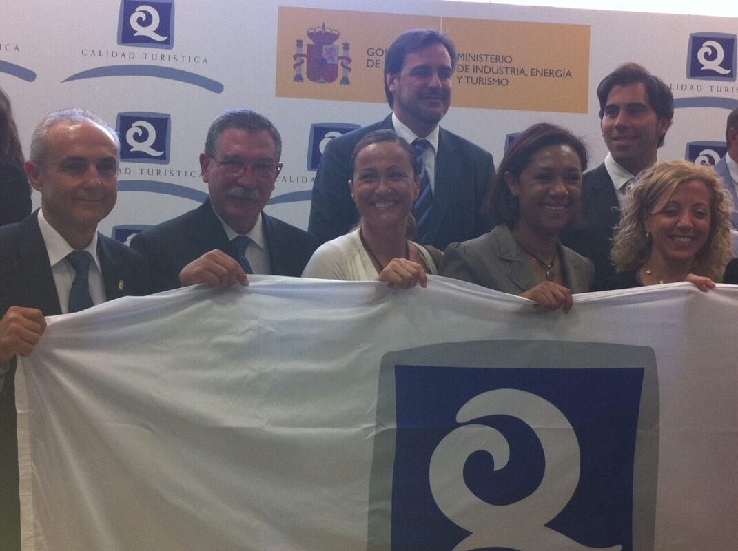 La concejal de Playas sostiene la bandera de Q de calidad con otros ediles