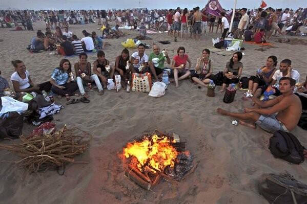 Un grupo de jóvenes ante una hoguera en la playa de la Malvarrosa