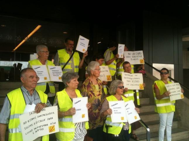 El grupo de yayoflautas en la puerta de Bankia con carteles de protesta/mov. yayoflautas