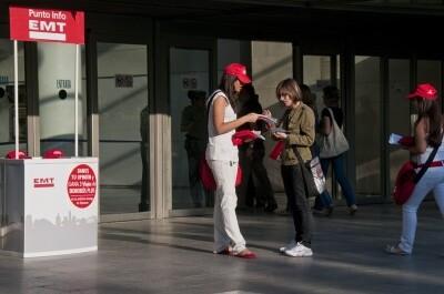 Una joven reparte información de la EMT en la calle