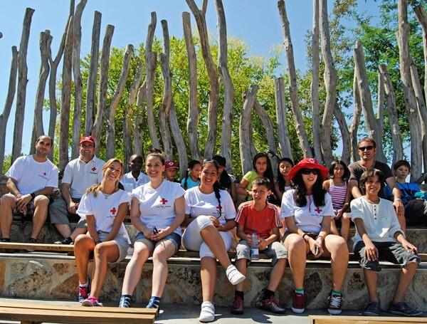 Voluntarios de la Cruz Roja junto a los niños de San Ildefonso antes de la exhibición educativa de Bioparc Valencia