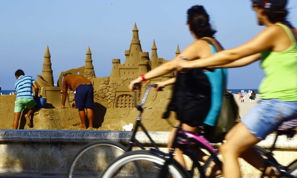 Dos ciclistas pasan por delante de una de las esculturas de arena
