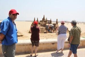 Varias personas observan el gigantesco castillo de arena de ocho metros/josep v. zaragoza