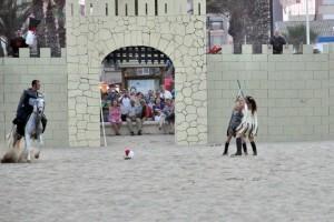 Dos personajes luchan encarnizadamente delante de la muralla