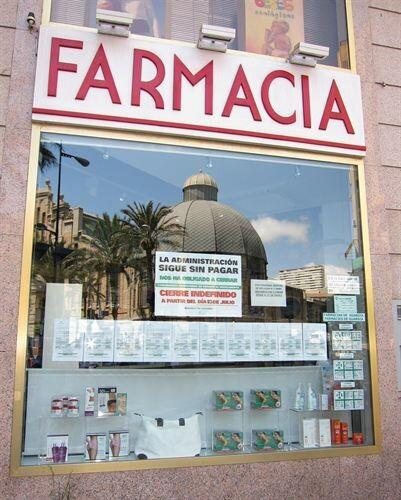 Una farmacia con un cartel de protesta por el retraso en los pagos/e.p.