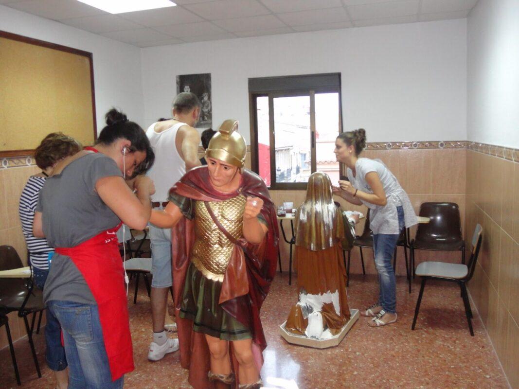 Varios cofrades de la Corporación de Longinos retocan las imágenes en el salón parroquial de la iglesia de los Ángeles del Cabanyal