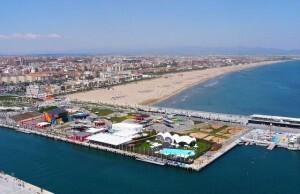 En primer plano una zona de la Marina Real con el paseo marítimo y la playa de Las Arenas de fondo