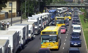 A la izquierda, comitiva de vehículos en la procesión a San Cristóbal en la avenida del Cid