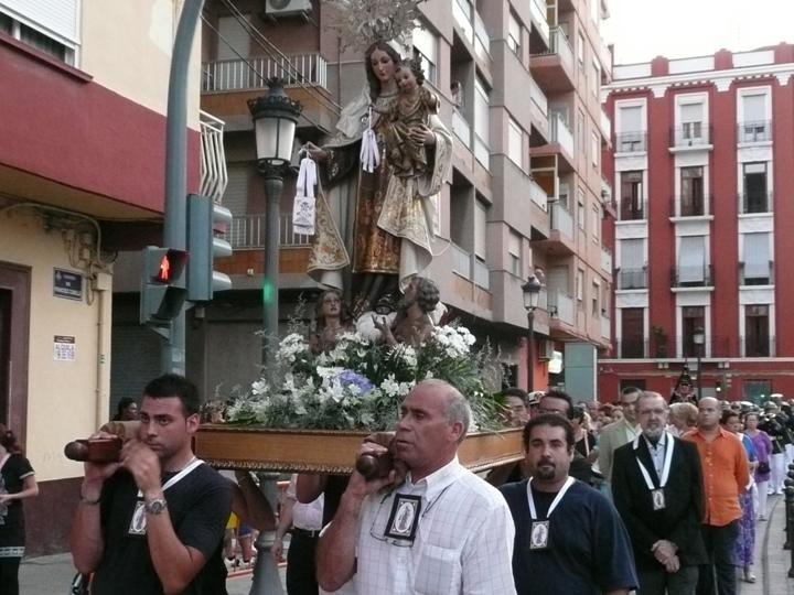 Un grupo de cofrades lleva a hombros a la Virgen del Carmen en el Grao