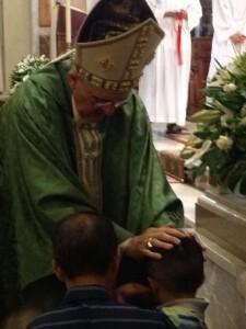El arzobispo bendice a uno de los niños asistentes/j.b.a.