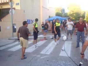 Dos policías locales apartan a la gente segundos después de caer la farola por el paso de la carroza/vlcciudad