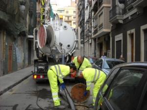 Varios operarios limpiezan un tramo de la red de saneamiento