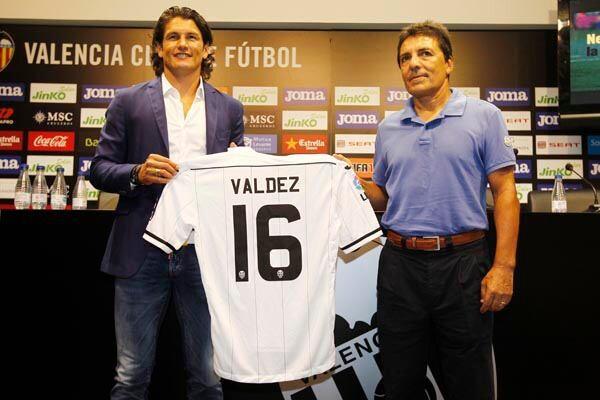 El nuevo jugador Nelsón Valdez sujeta su camiseta mientras por el otro lado la ase el valencianista Rubén Valdez/vcf