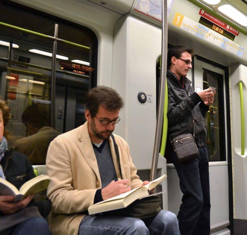Un usuario del metro lee mientras realiza el desplazamiento/gva