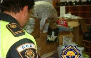 Una agente de la Policía Local de Valencia observa un grupo de fardos de prendas falsificadas en otra operación/plv