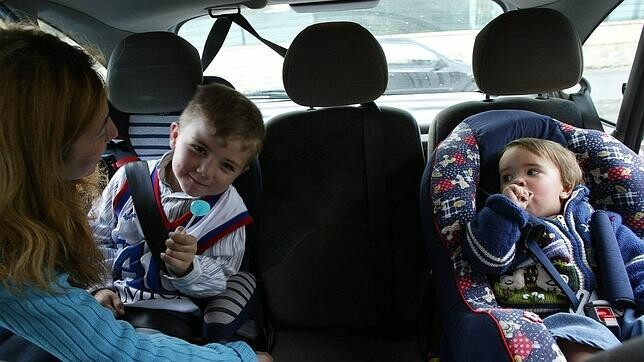 Dos niños en sendas sillas en el asiento trasero de un vehículo