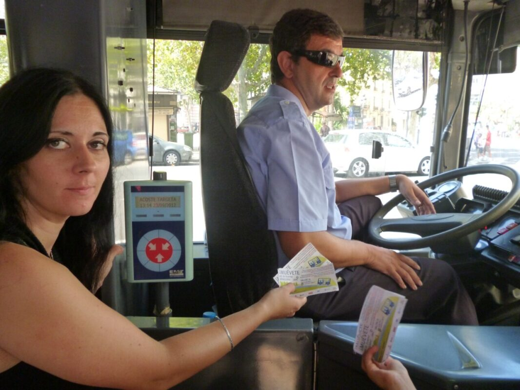 Un pasajera enseña el billete al conductor de bus/emt