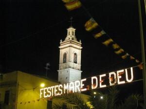 Vista de la torre de la iglesia de San Isidro con el cartel luminoso anunciando los festejos