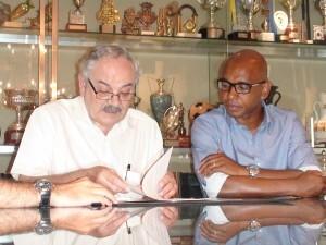 El presidente de la federación de fútbol de la C.V. y Marcos Senna firmando el acuerdo/ffcv