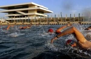 Un grupo de triatletas en la prueba de natación pasa por delante del Veles e Vents