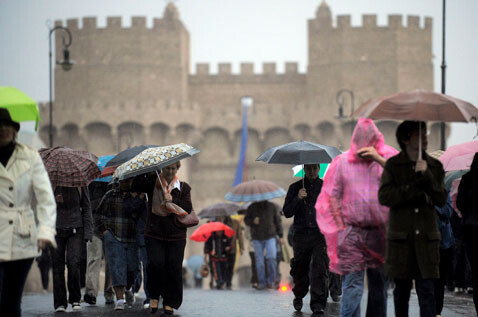 Un grupo de personas se guarece de la lluvia con paraguas en el puente de Serranos