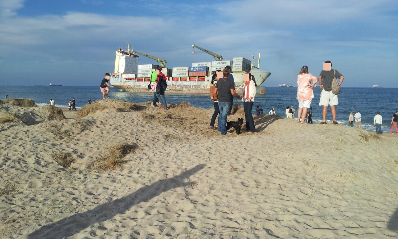 Zona de la playa de El Saler con personas en las dunas y uno de los barcos varados enfrente/compromís