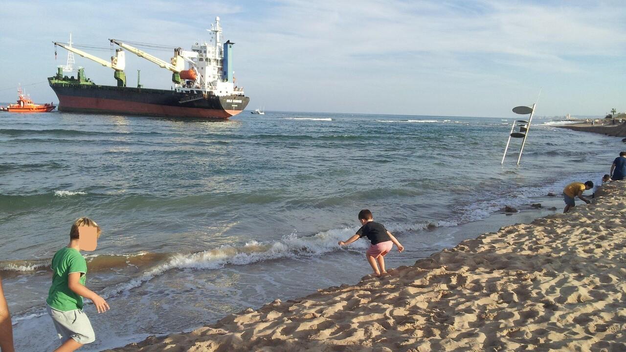 Unos niños juegan donde hace unas semanas había playa mientras siguen los trabajos para reflotar los barcos/Compromís