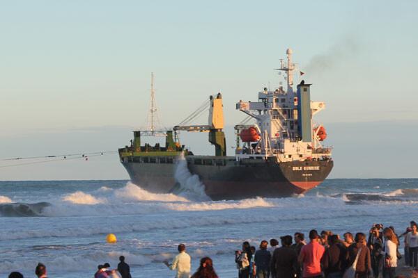 El buque Sun Rise, tirado por dos remolcadores de Salvamento Marítimo, pugnando por salir del Saler