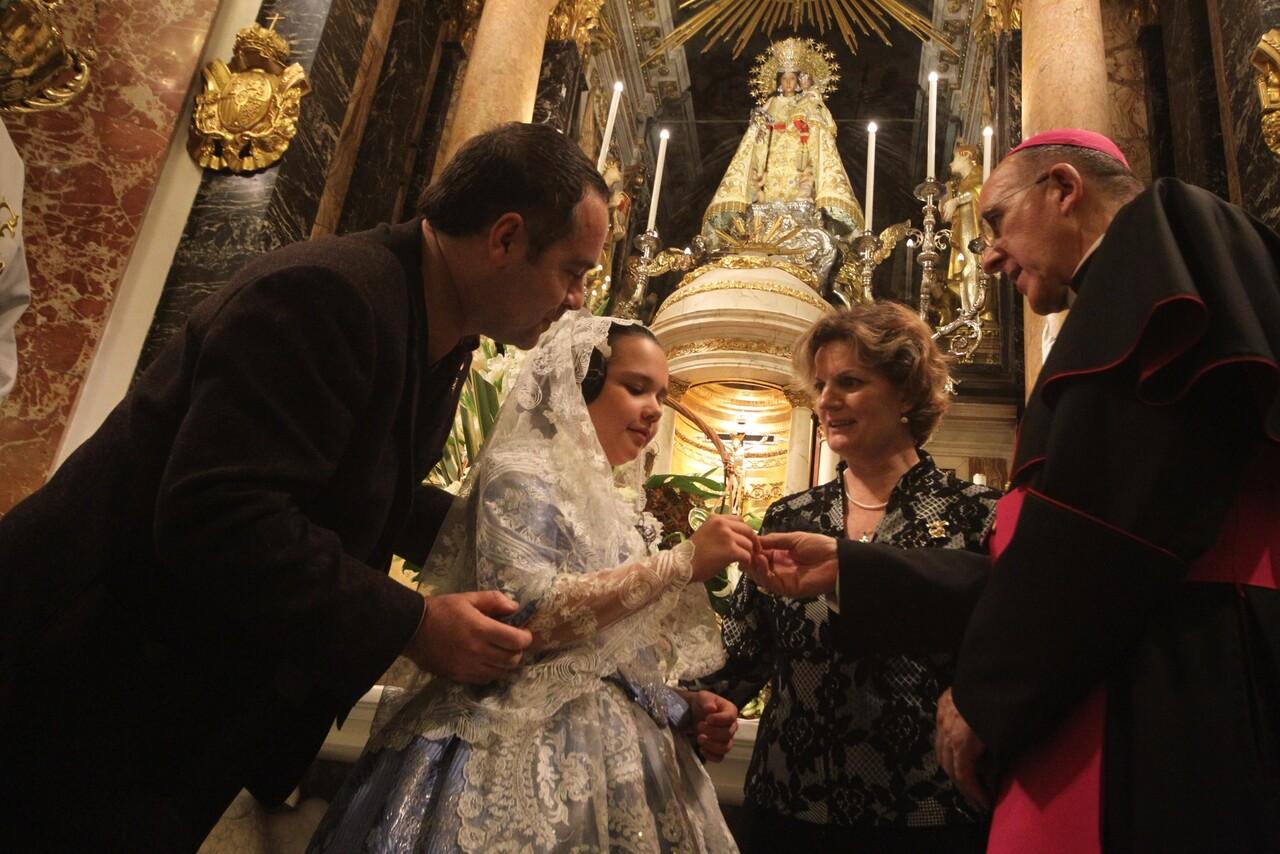 Una niña vestida de valenciana entrega la insignia en presencia de la presidenta de los belenistas valencianos y del arzobispo/javier peiró/avan