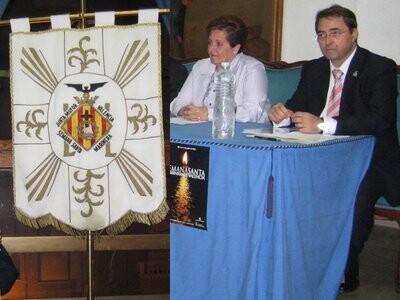 La presidenta de la Semana Santa Marinera en la presentación de un cartel de años pasados junto al estandarte y el secretario general, Mariano Pascual, de aquel año/eos