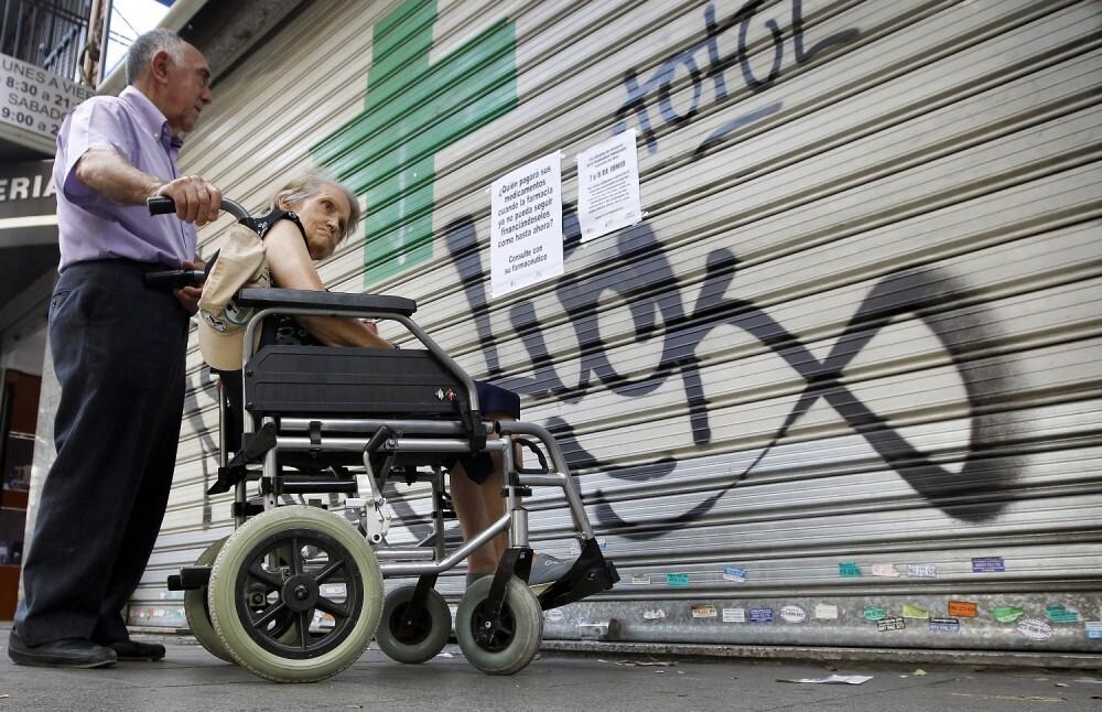 Una mujer en silla de ruedas se encuentra con las puertas cerradas de una farmacia/gtres