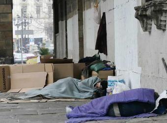 Varias personas duermen en una calle al aire libre