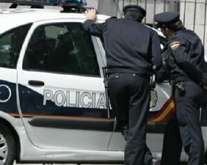 Dos agentes de la policía nacional habla con un compañero de patrulla en un vehículo/cnp