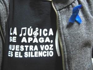 Un lazo azul en la solapa de un asistente al acto/c.e.