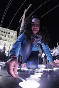 Una joven enciende una vela en la plaza de la Virgen/a.saiz
