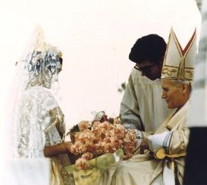 Una joven vestida de valenciana entrega unas flores al Papa Juan Pablo II