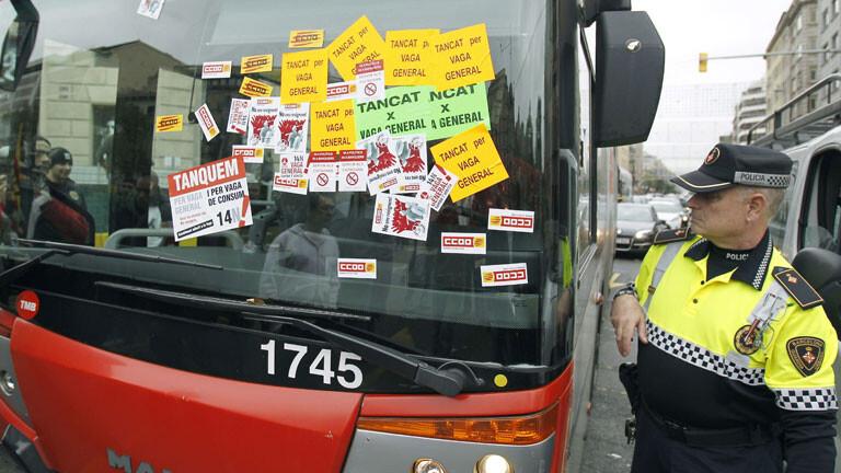 Un policía de una ciudad observa un bus de transporte público en la jornada de ayer