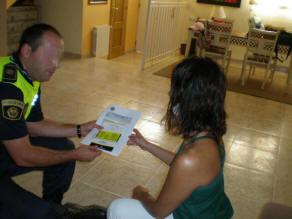 Un policía local del grupo Gama explica un folleto a una mujer/plv
