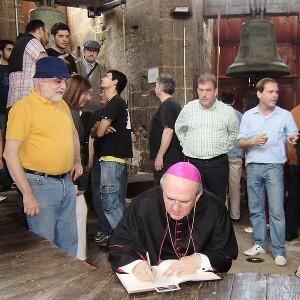 Francesc Llop, a la izquierda, observa como el arzobispo firma en el libro de oro de la asociación en la sede, en el Micalet/avan