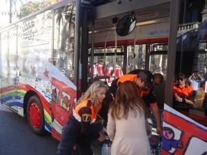 Varios voluntarios descargan los alimentos del bus de la EMT/EMT
