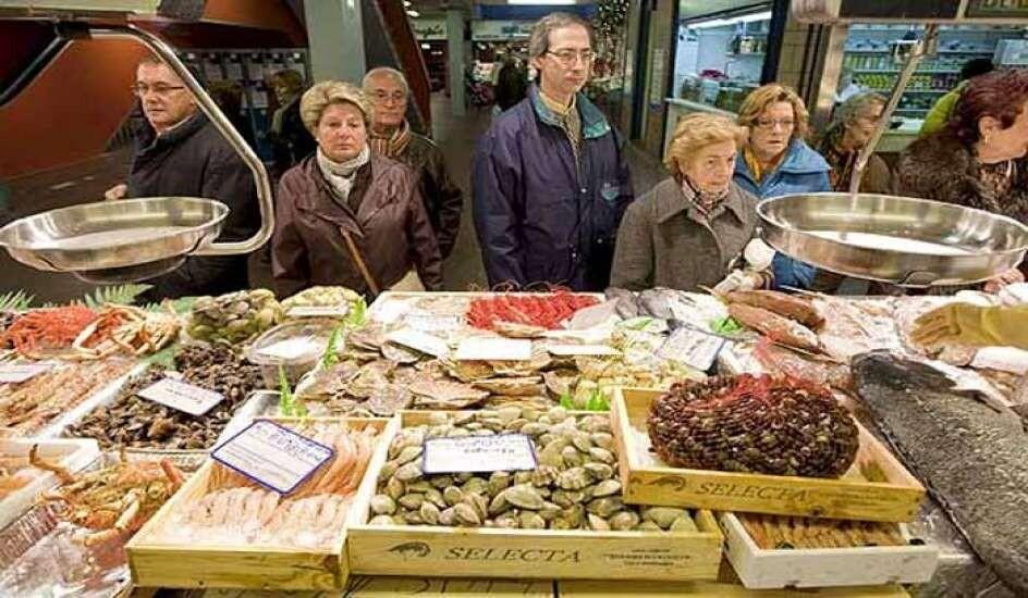Varias personas hacen cola para comprar en un mercado/20minutos