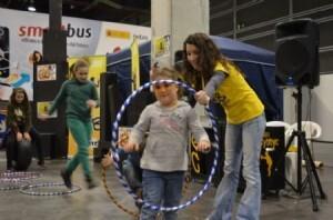 Una monitora del área de Deportes Urbanos anima a una niña a pasar el hula hop/josep v. zaragoza