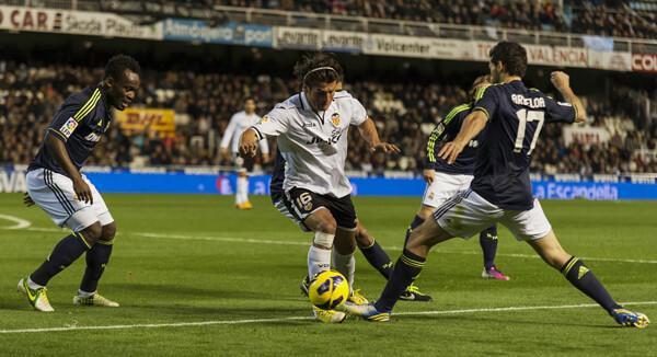 Nelson Valdez intentando progresar ante varios jugadores del Madrid.